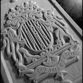 Gravure dans la pierre naturelle d'armoiries familiales en bas-relief.