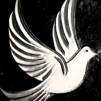 Gravure à la main d'un motif en forme de colombe sur une stèle de granit en cimetière.