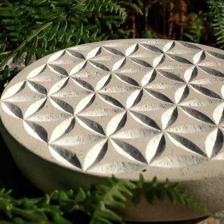 Fleur de vie, symbole de géométrie sacrée, gravée dans une coupe de pierre façonnée à la main.