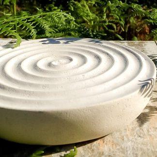 Gravure à la main de manière traditionnelle d'une spirale dans la pierre, puis façonnée en forme de coupe.