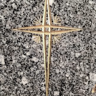 Gravure manuelle sur stèle en granit poli d'une croix catholique dorée à la feuille d'or 24 carats.