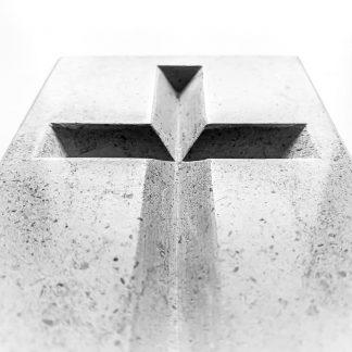 Photo noir et blanc d'une croix catholique gravée à la main dans la pierre naturelle calcaire.