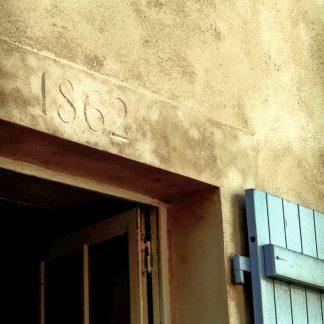 Date de construction de maison gravée à la main dans la façade, au dessus de la fenêtre.