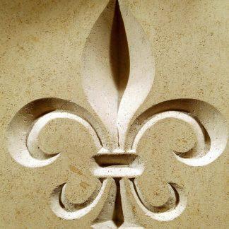 Fleur de lys gravée en relief dans une dalle de pierre naturelle calcaire, avec des outils traditionnels de gravure.