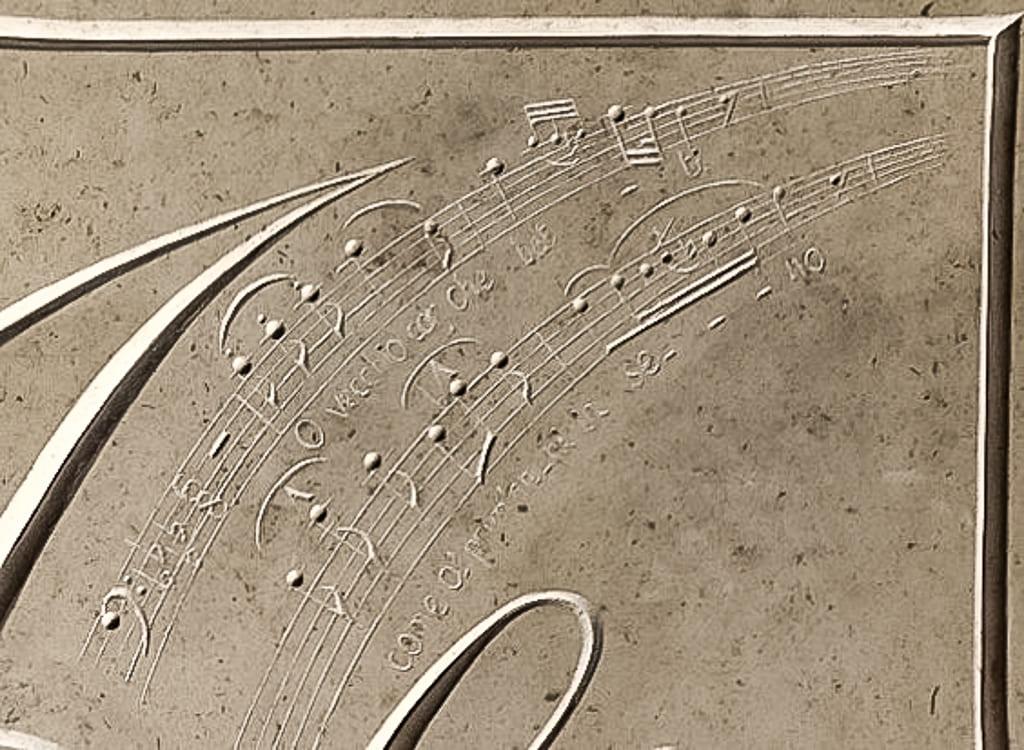 Détail d'une plaque gravée dans la pierre pour un projet sur mesure mettant en avant une partition musicale.