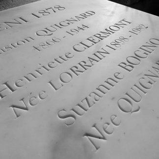 Gravure d'épitaphes dans une dalle de marbre blanc sur une sépulture funéraire, avec des outils traditionnels de gravure artisanale dans la pierre.