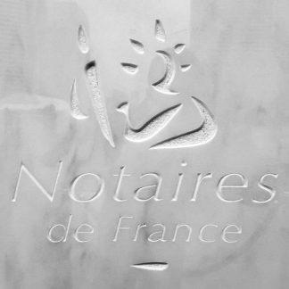 Gravure à la main avec outils traditionnels du logo des notaires de France, dans une dalle de marbre blanc polie.