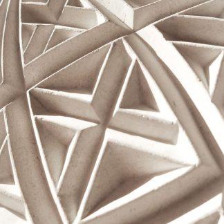 Motif géométrique gravé à la main dans la pierre naturelle.