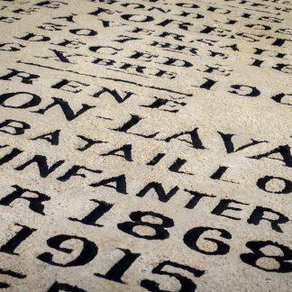 Peinture en noir des lettres gravées dans la pierre naturelle sur une sépulture de famille.