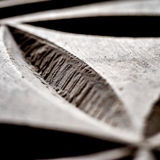 Rosace d'une fleur de vie gravée dans la pierre en vue macro.