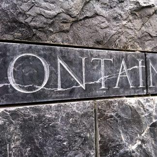 Photo d'une gravure à la main faisant office de signalétique des fontaines du sanctuaire de la ville de Lourdes.
