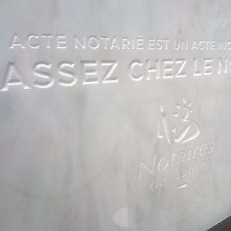 Texte et logo des notaires de France gravés sur une dalle de marbre blanc.