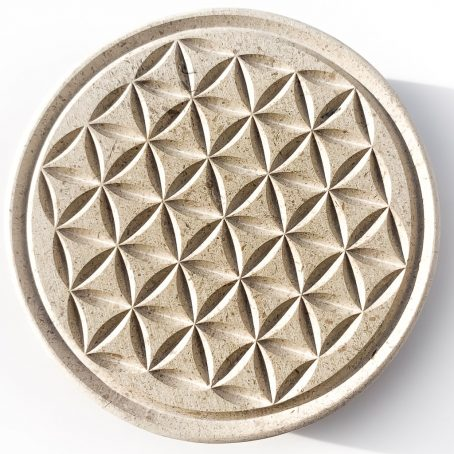 Gravure dans la pierre d'une fleur de vie ronde vue de dessus.
