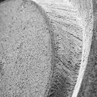 photo noir et blanc d'une lettre gravée dans la pierre à la main de manière artisanale