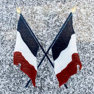 drapeaux français croisés bleu-blanc-rouge gravés à la main dans le granit sur un monument aux morts