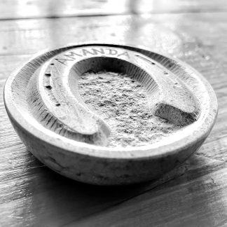 photo noir et blanc d'une pierre calcaire ronde en coupelle gravée à la main, en forme de fer à cheval