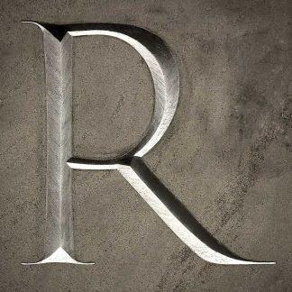 Lettre R typographie Trajan gravée dans la pierre naturelle