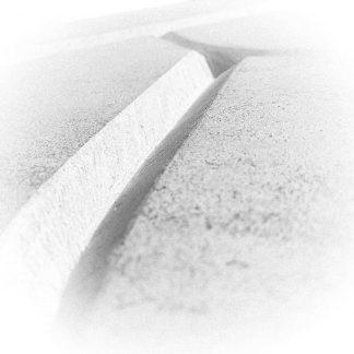 photo noir et blanc d'une gravure dans la pierre à la main.
